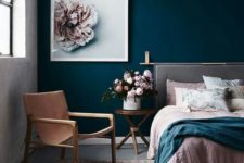18 a chic bedroom done with a navy statement wall, a blush rug and bedding looks very inviting