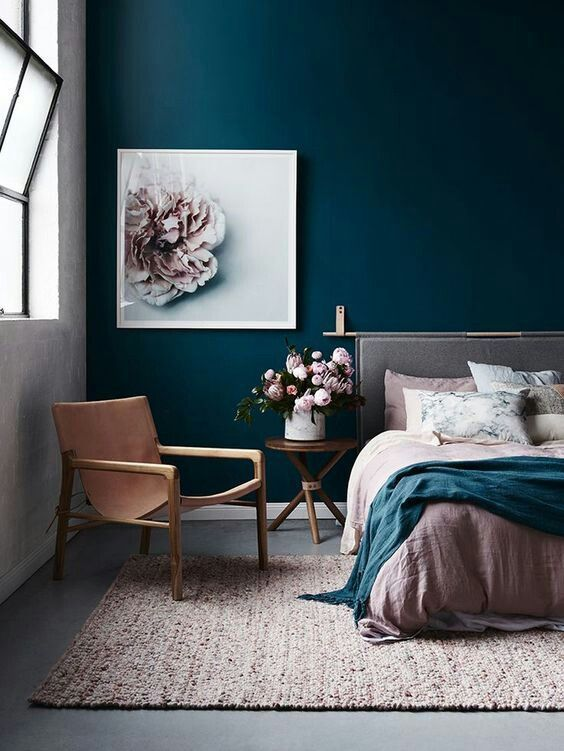 a chic bedroom done with a navy statement wall, a blush rug and bedding looks very inviting