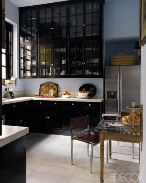 a refined kitchen with black cabinets and smoked glass upper cabinets plus white countertops for a contrast