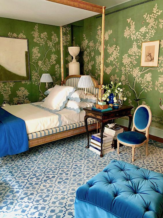 a sophisticated bedroom with botanical print wallpaper and medium blue accents - a chair, an ottoman and a blanket