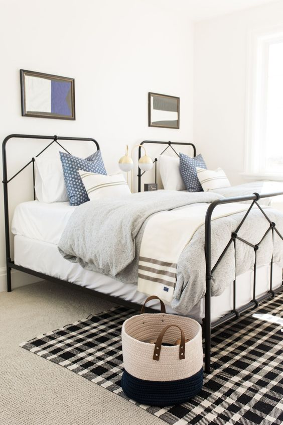 a stylish gender neutral guest bedroom with two beds and touches of black here and there for drama