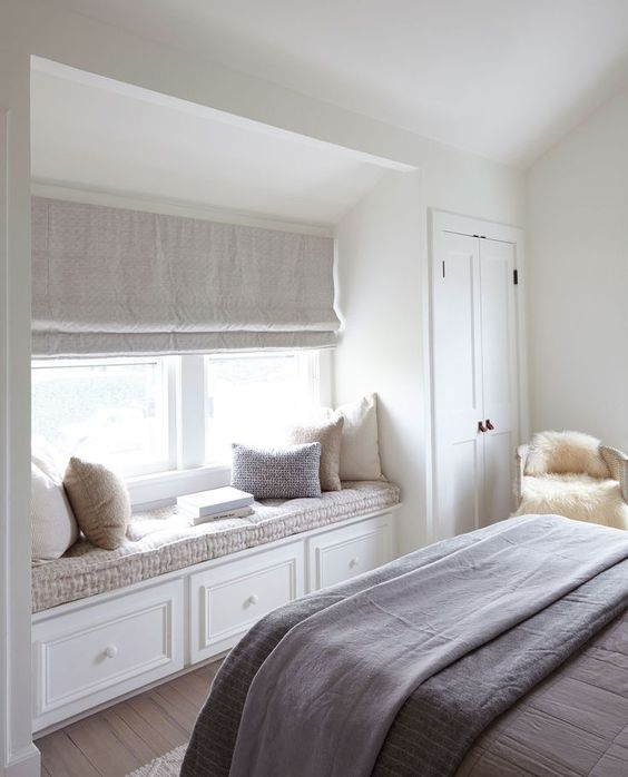an upholstered window sill with storage is a stylish idea for a bedroom that doesn't have much space
