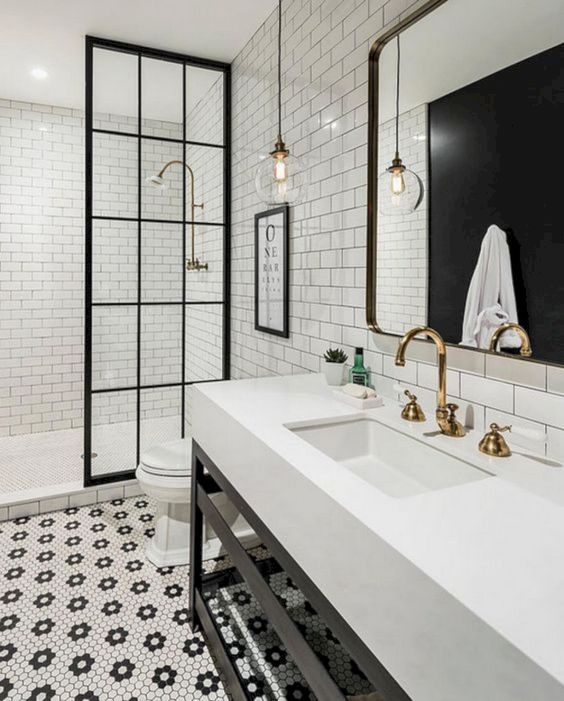 hex penny tiles forming floral patterns on the floor and neutral white subway tiles with black grout on the walls