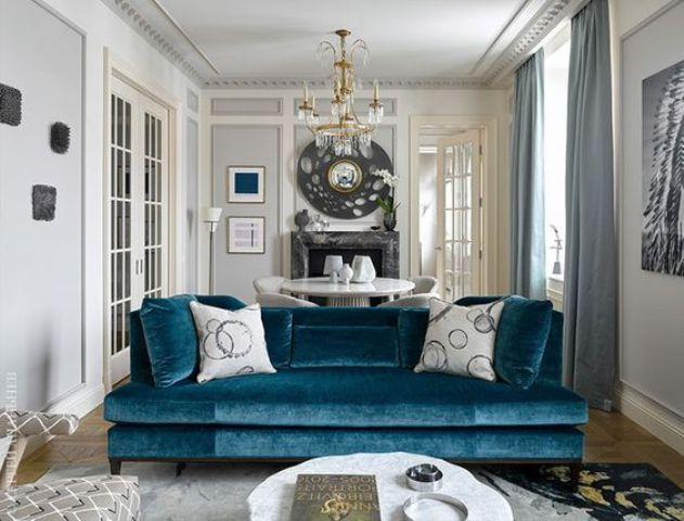 a medium blue velvet sofa brings color to the space yet keeping it calm and relaxing enough