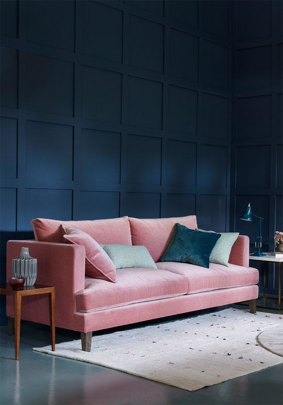 a refined living room with a navy statement wall and a pink velvet sofa plus green pillows
