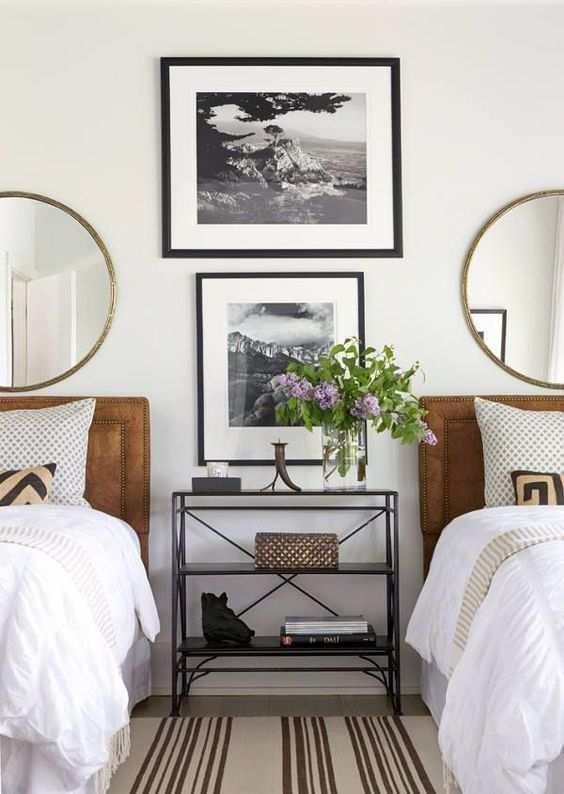 a stylish gender neutral guest bedroom with leather upholstered beds and round mirrors plus artworks