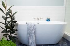 19 navy hex tiles on the floor ad white tiles on the walls create a bold and catchy combo for a modern bathroom