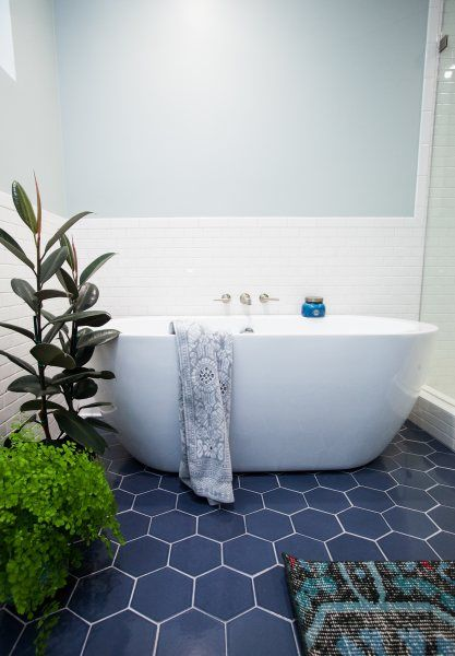 navy hex tiles on the floor ad white tiles on the walls create a bold and catchy combo for a modern bathroom