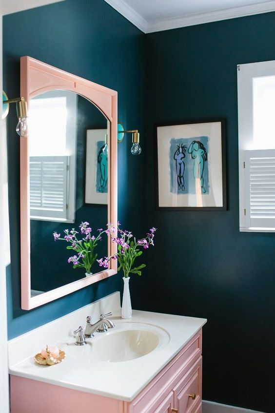a navy bathroom with a blush mirror and a blush vanity plus brass touches here and there