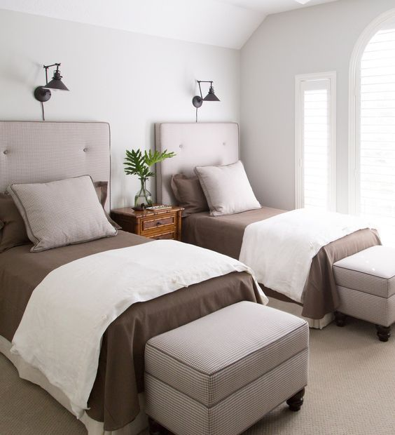 a stylish modern guest bedroom with two beds, storag eottomans and some wall lamps