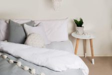 20 layered blankets with pompoms and crochet and knit pillows make the bed very inviting