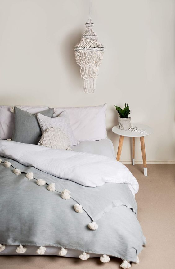 layered blankets with pompoms and crochet and knit pillows make the bed very inviting