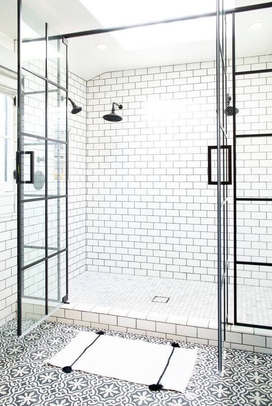 white subway tiles with black grout on the walls make up a cool combo with black and white mosaic tiles on the floor