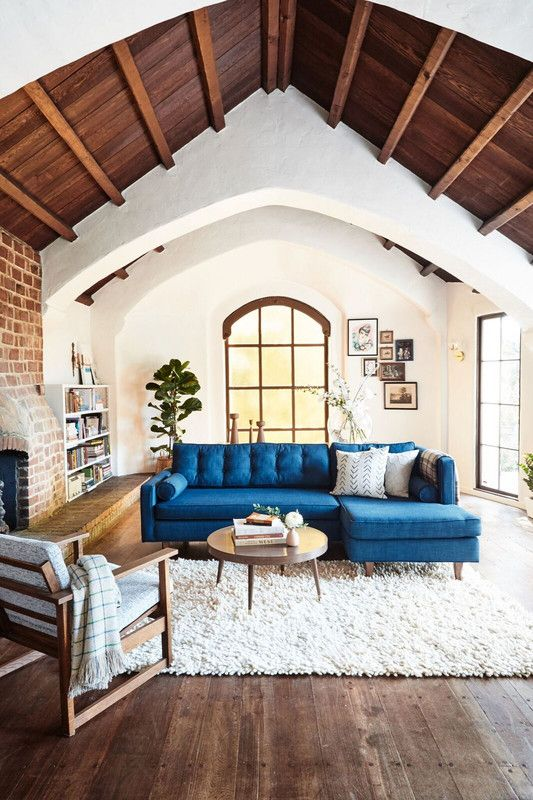 a bright blue L shaped sofa adds color and interest to the space becoming its centerpiece