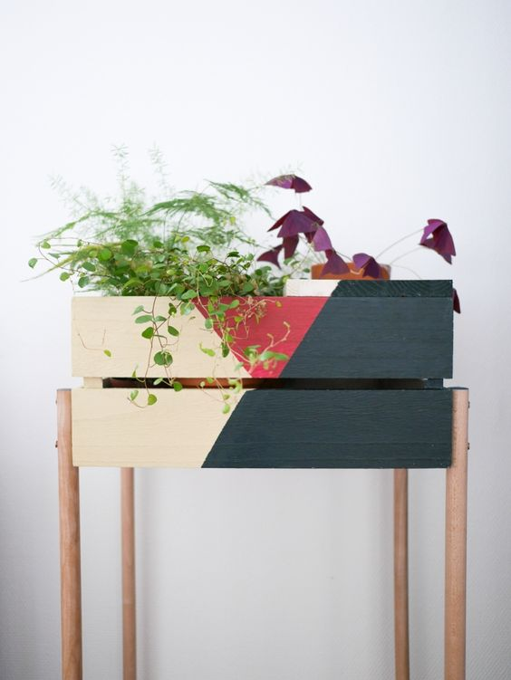 a color block Knagglig box placed on wooden legs can become a cool plant stand