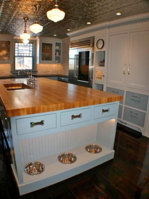 a kitchen island with an additional pet food station with lights and drawers for dog accessories