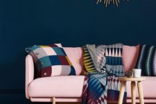 21 a sophisticated living room with a navy statement wall, a bold modern pink couch and colorful accessories