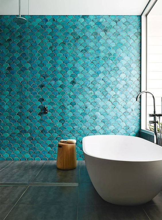a bold turquoise fish scale tile wall is a statement in the bathroom, and neutral grey tiles on the floor