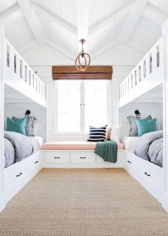 a cozy beach-inspired guest bedroom with two bunk beds and a windowsill daybed