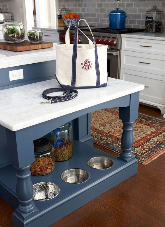 a kitchen island with an additional table and a dog feeding station and supplies organizer in its lower part