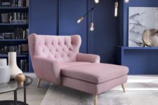 22 a mid-century modern living room with navy walls and a blush lounger looks bold and fresh