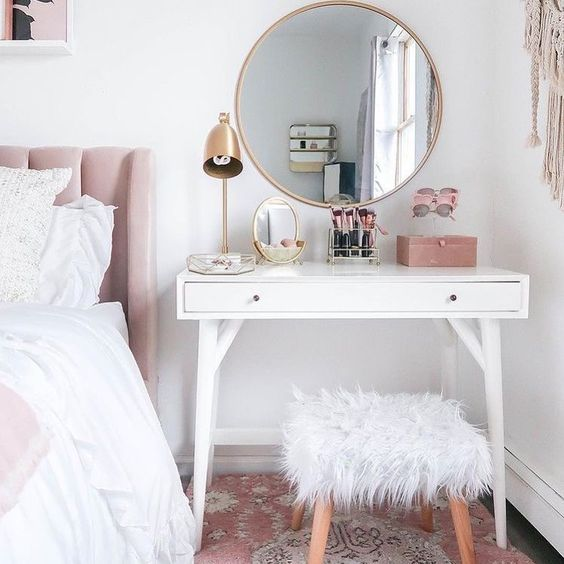 a simple dressing table that doubles as a bedside table with a stool covered with faux fur