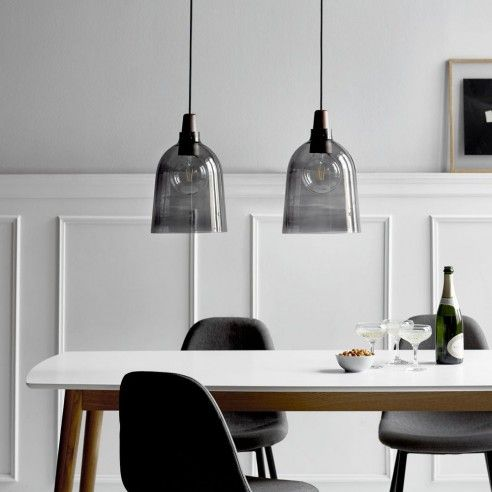 smoked glass pendant lamps over the dining table is bold and edgy idea to try