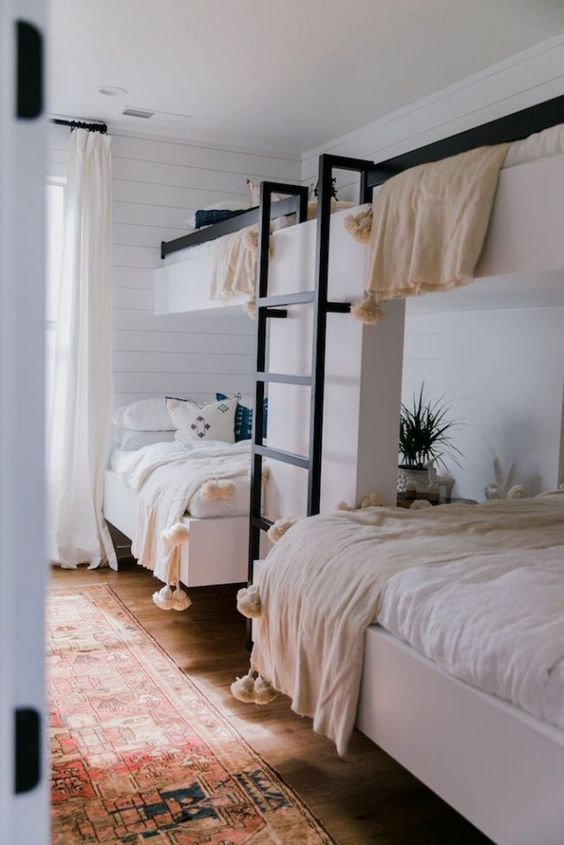 a cozy guest bedroom with two bunk beds and a ladder, with much natural light and pompom blankets