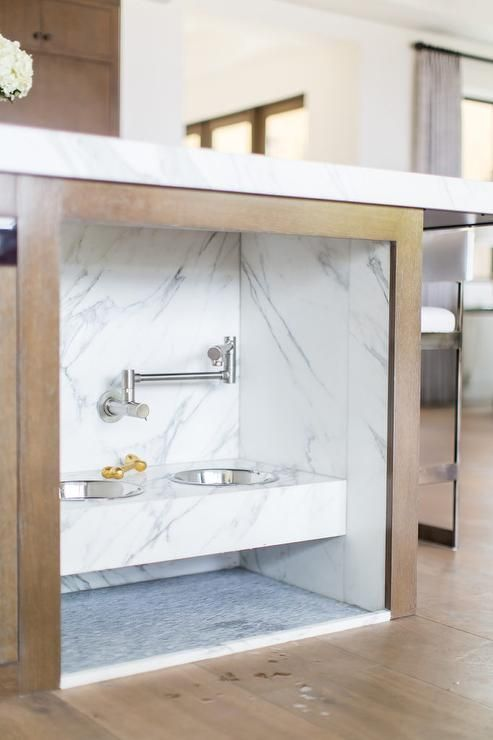a kitchen island with an integrated pet food station done with marble contact paper is a stylish idea