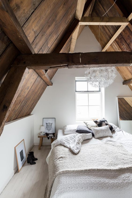 a large bed, a mirror and wooden bedside tables that echo with the sloped ceiling and beams