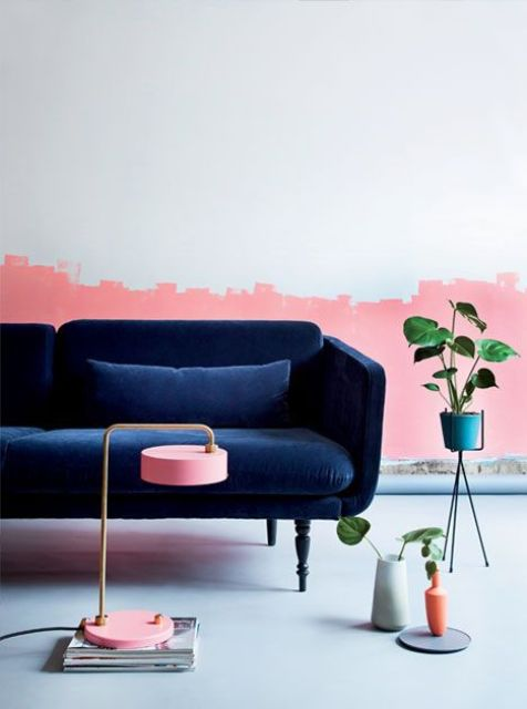 a living room with a catchy half pink wall and a refined navy velvet sofa