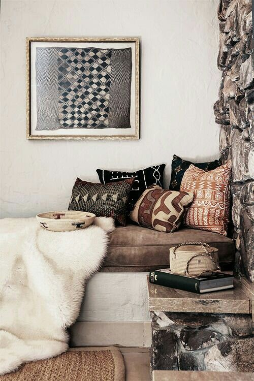 tribal printed pillows and a tribal basket and an artwork bring a wild feel to the space