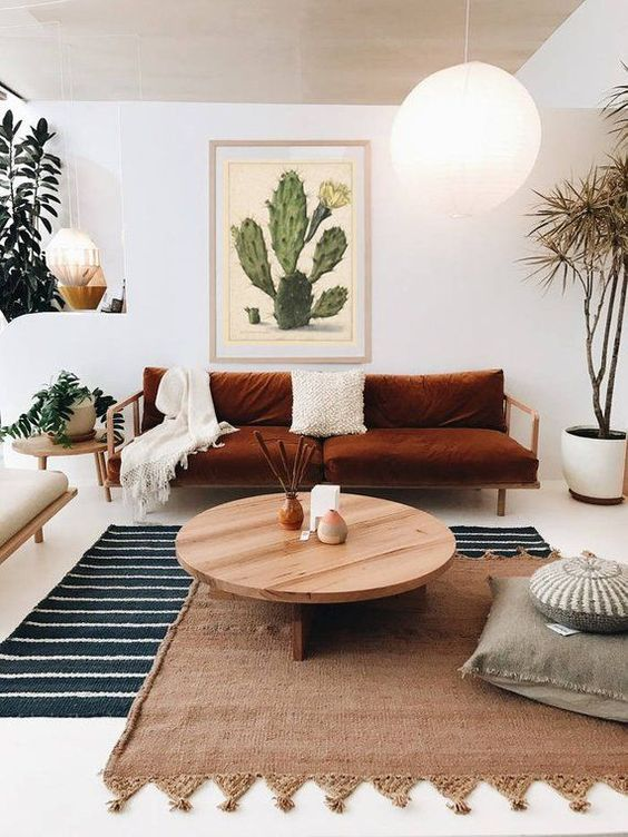 a striped rug, a woven one with tassels over it for a cool boho inspired living room