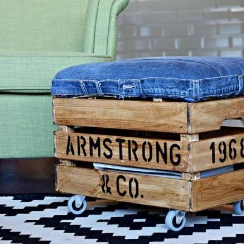 an industrial ottoman made of a stained Knagglig box with letters, with a denim seat and casters