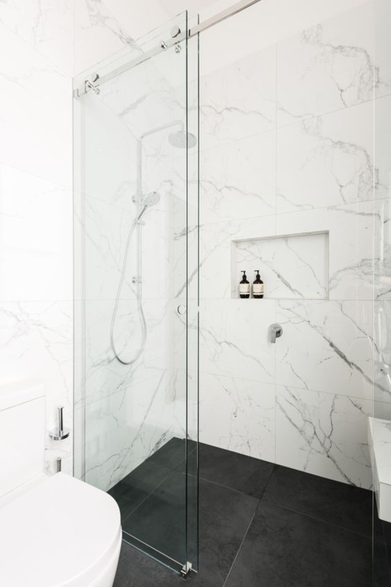 beautiful white marble tiles on the walls and black matte tiles on the floor create a stylish and timeless combo