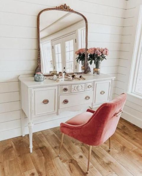 a vintage vanity and a pink upholstered chair by it as a colorful touch and a seating piece