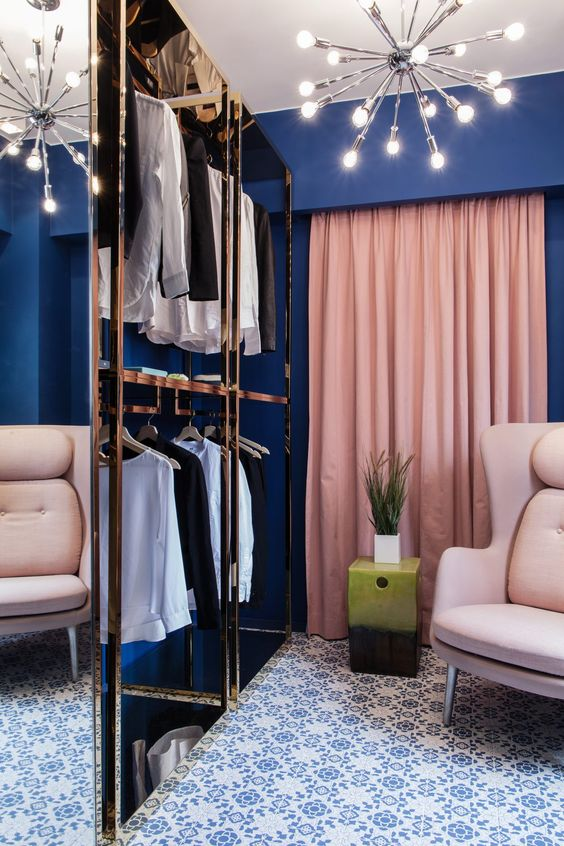 a navy closet with pink drapes and neutral furniture plus metallic touches looks very glam like