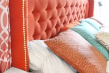 26 add a touch of color with a coral tufted headboard and decorative nails for a bold look