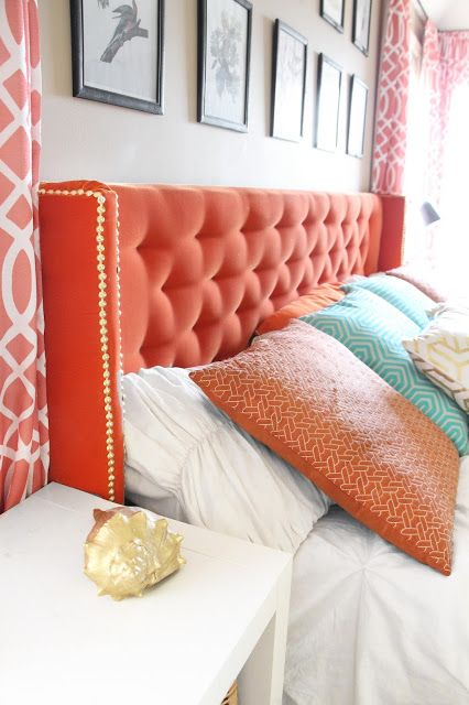 add a touch of color with a coral tufted headboard and decorative nails for a bold look