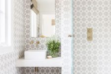 26 chic patterned mosaic tiles on the walls and neutral light grey ones on the floor plus brass accents