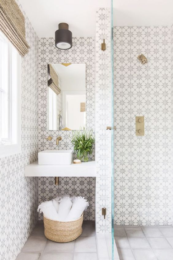 chic patterned mosaic tiles on the walls and neutral light grey ones on the floor plus brass accents