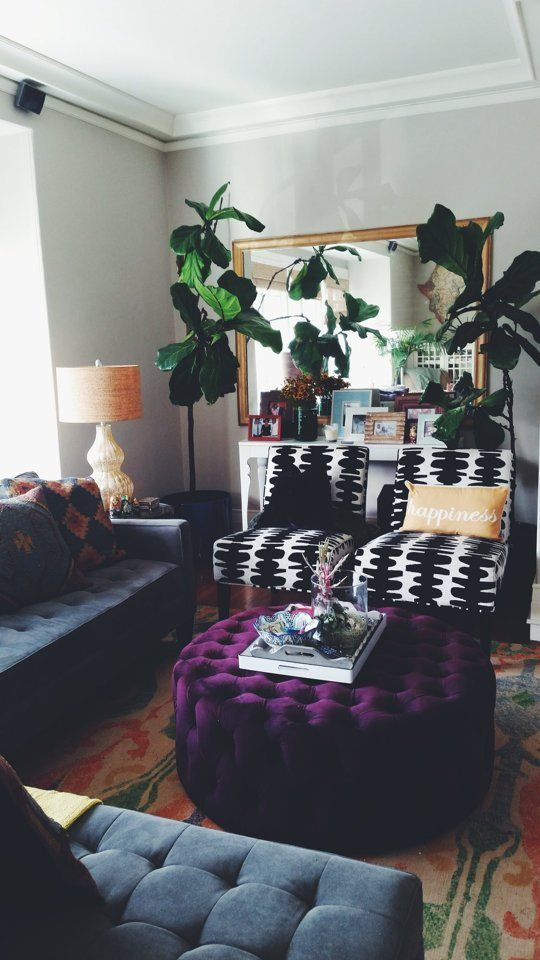 a plum colored tufted velvet ottoman with hidden storage adds color to the space