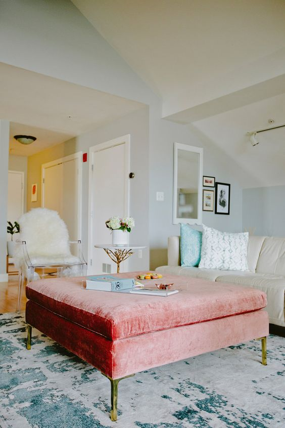 a peachy pink velvet ottoman with hidden storage can act as a coffee table or a seat