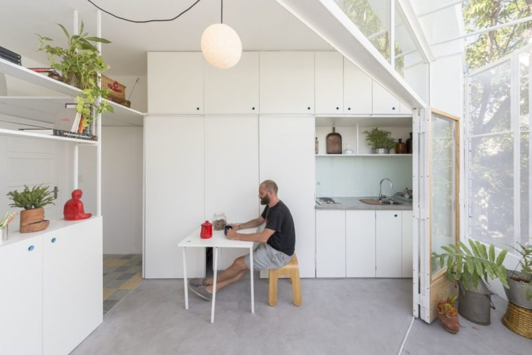 The apartment features a white sleek kitchen with a small eating space that can be hidden