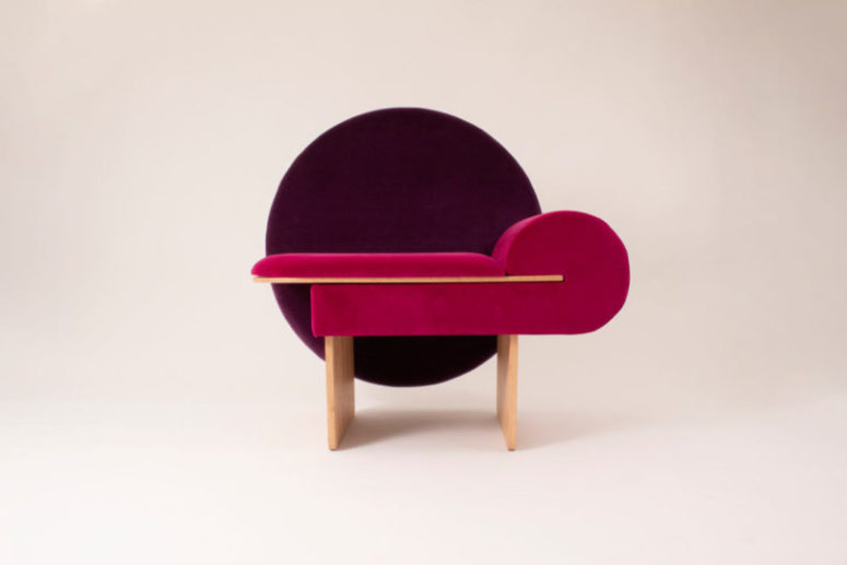 The base is made of wood, the chair is upholstered in hot pink and the back is a purple circle