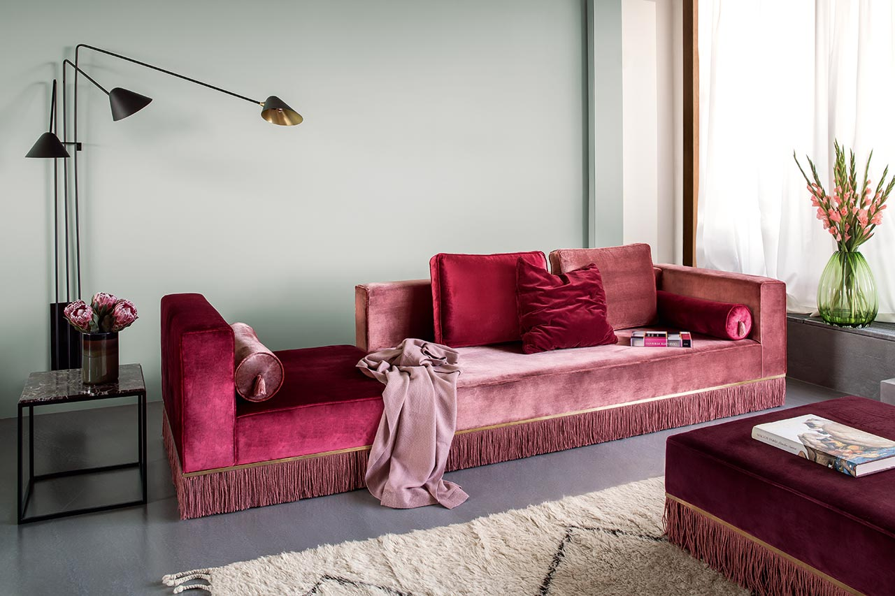 The living room is styled with adorable velvet furniture in jewel tones with fringe