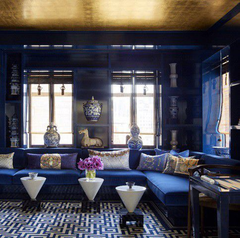a bold and exquisite living room in electric blue spruced up with a gold ceiling and gold touches