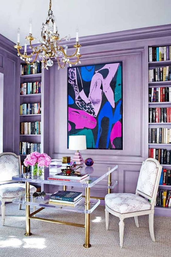 a bold glam living room with lilac walls and built-in shelves and a bright artwork is filled with tender colors