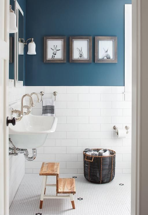 a contemporary bathroom with walls partly painted blue and partly clad with white tiles