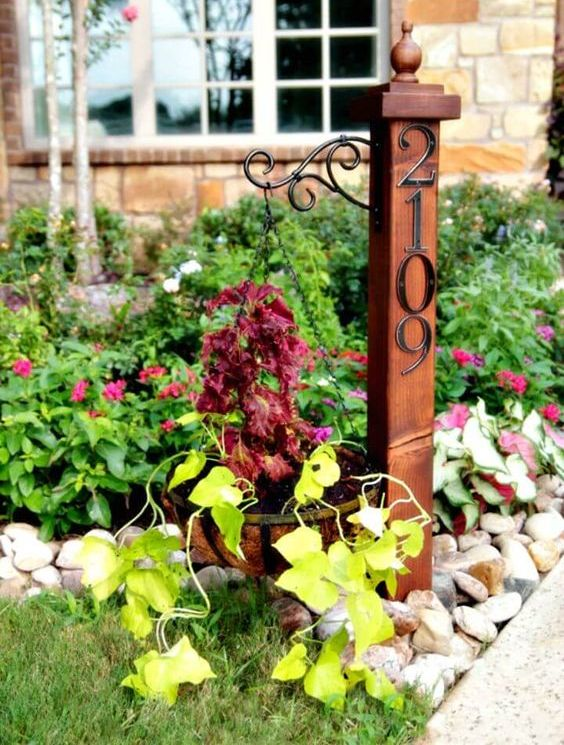 a garden post with a hanging planter and elegant metal house numbers is a stylish vintage-inspired idea